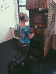 Feminist Confessional arcade cabinet with prayer bench